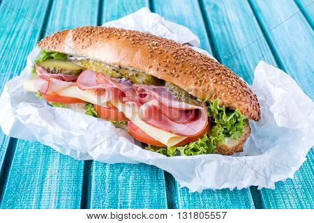 Photos of submarine sandwich packed on rustic background