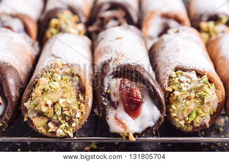 Photos of sweet homemade cannoli on rustic background