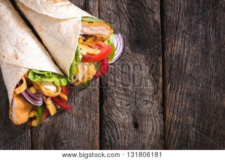Tortilla sandwiches with fried chicken on rustic background