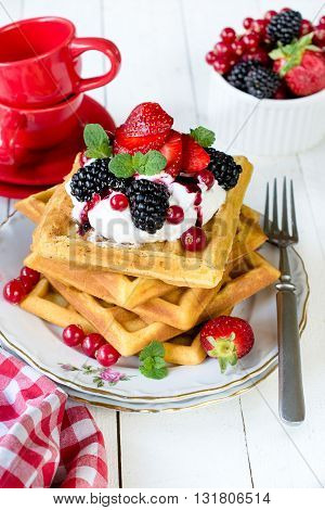 Waffles and berry fruits on rustic background