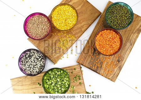 Multicolored clear glasses with various legumes ( green peas red lentils canadian lentils indian lentils black lentils green lentils green mung beans) on white and wooden background