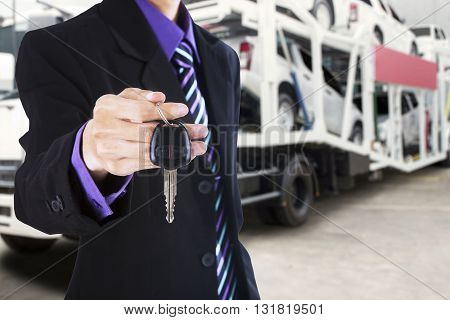 Businessman hand giving a car key with a trailer truck carrying new cars on the background