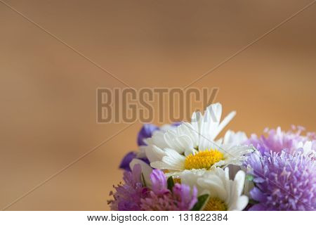 background with hand picked garden flower blossoms on brown