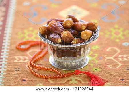 Arabic dates in a glass bowls and muslim prayer beads. Ramadan stock photo.