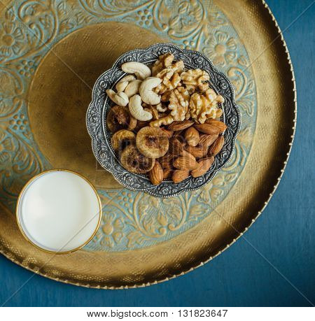 Bowl of mixed nutritious nuts and glass of fresh milk. A healthy food for breaking Ramadan Fast.