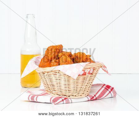 Wicker basket filled with spicy buffalo style chicken wings.