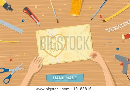 View from the top of table with instruments for hand made. Woman making gift card. Hands of woman. Tools for scrapbooking lying on a table.