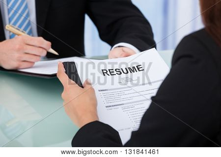 Cropped image of female candidate holding resume at desk during interview