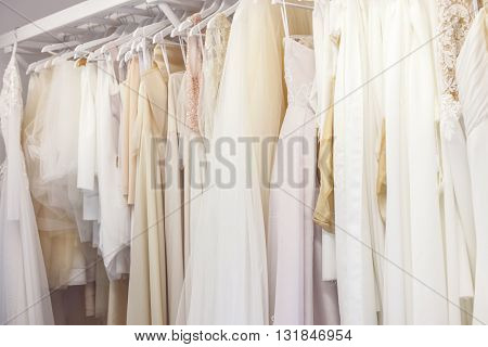 Beautiful wedding dresses hanging on stand in salon