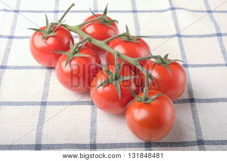 Bunch Of Tomatoes On A Branch On Squared Cloth Table