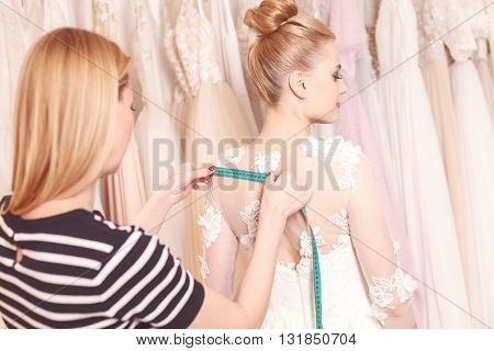 Skillful designer is taking measurements of wedding dress on young girl. She is standing and holding tape-measure on her back. The bride is dreaming happily
