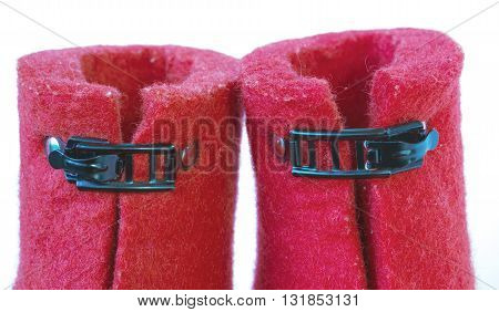 Iron clasps on the felt red boots on white background