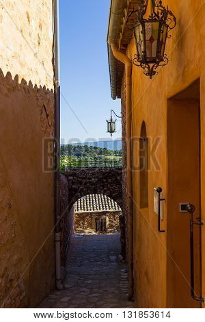 ROUSSILLION, FRANCE - MAY 17, 2015: This is narrow street in village Roussillion in Provence which is soaked with ocher from the nearby quarry.