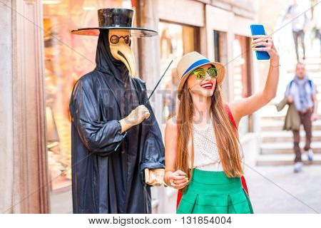 Young female traveler making selfie photo with traditional venice doctor manikin with mask and black costume on the street in Venice