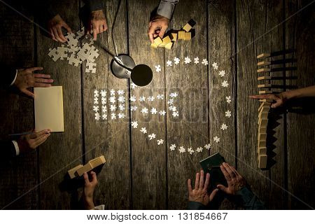 Teamwork and research concept - top view of six business people male and female working together on a project by using wooden pegs dominos and cubes making notes and matching puzzle pieces.