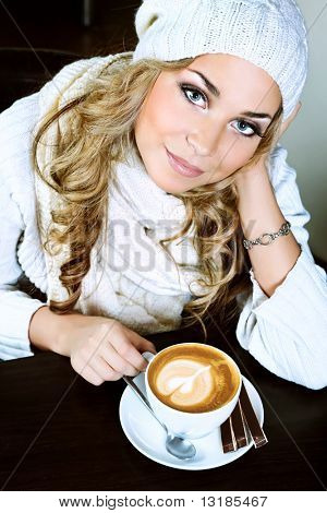 Beautiful young woman with a cup of tea at a caf poster
