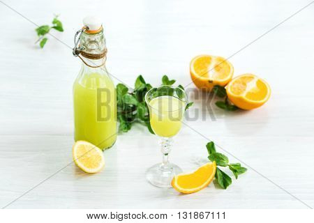 Home orange liquor in a glass and fresh oranges on the white wooden background in rustic style, selective focus