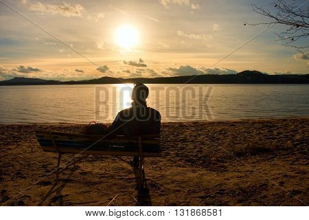 Alone Young Man In Silhouette Sitting In The Sun On Beach. Tourist  Take Rest On Wooden Bench At Aut