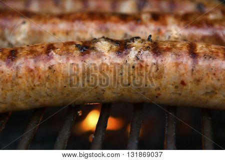 Spicy Italian pork sausages cooking on a backyard grill. Images shows the grill flame and bubbling delicious and nearly ready to eat meat.