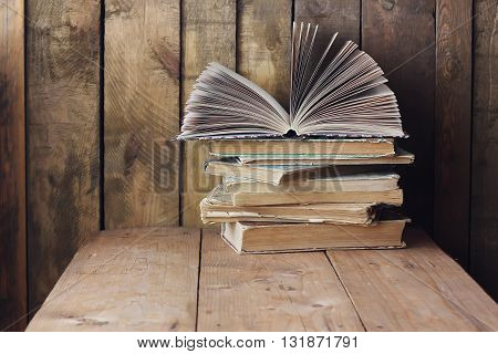 The stack of books on table on wall background from boards. An open book. Still life with books.