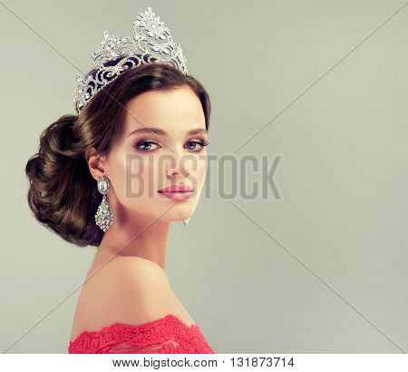 Beautiful model with elegant hairstyle . Beautiful woman with fashion wedding hairstyle with trend makeup . Jewelry crystal earrings .  Beauty Queen , a pretty girl with a crown on his head