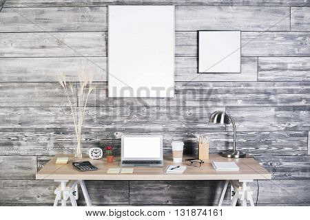 Interior with blank white laptop and various stationery items on creative designer desktop and blank picture frames on wooden wall. Mock up