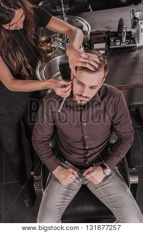 Top view of female barber shaving a client's beard while sitting in a chair in a barber shop