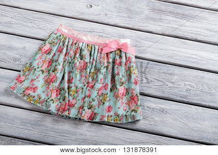 Casual skirt with flower print. Short skirt on wooden background. Colorful clothing item on shelf.