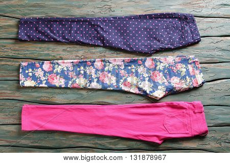 Different color female pants. Brigh pink and navy trousers. Selection of pants in shop. Variety of patterns.