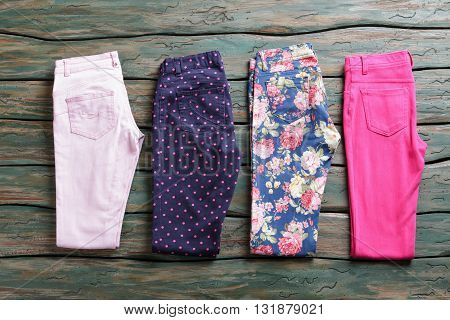 Folded pants of different color. Summer trousers with print. Imported merchandise in store. Quality garments for women.