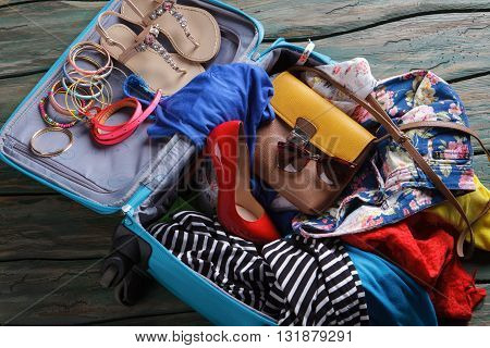 Red heel shoe in suitcase. Crumpled clothes in luggage bag. There's never enough space. Consider buying a bigger suitcase.
