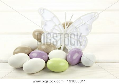 Colorful sugared almonds and papery butterfly on white wooden background