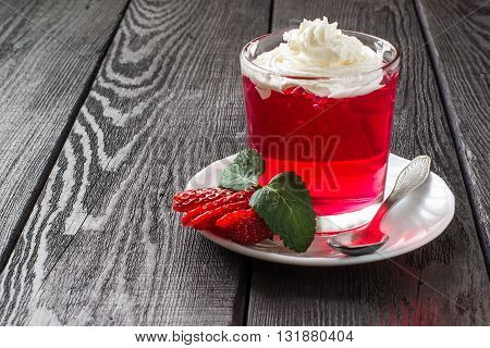 Delicious strawberry jelly with whipped cream in a glass and ripe strawberries on a plate on dark wooden table. Selective focus