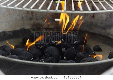 black coal briquettes on fire at barbecue event