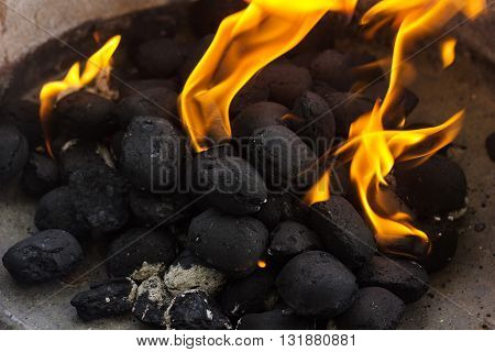 black coal briquettes on fire at barbecue place