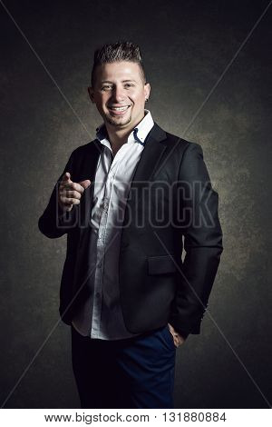 elegante smiling businessman with jacket pointing with finger