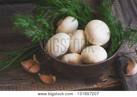 bowl with mushrooms and herbs on an old wooden background tinted