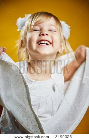 Adorable little blonde girl in a white dress . The girl was only three years-Isolated on yellow background