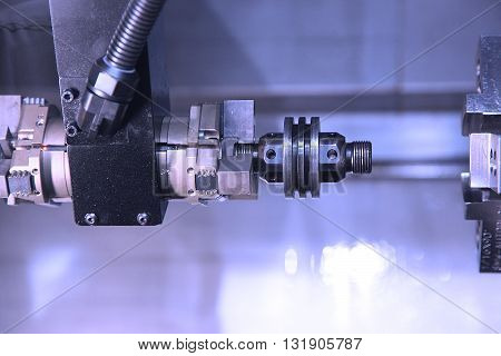 Automatic feeding metal parts processing on lathe in workshop. Selective focus on tool poster