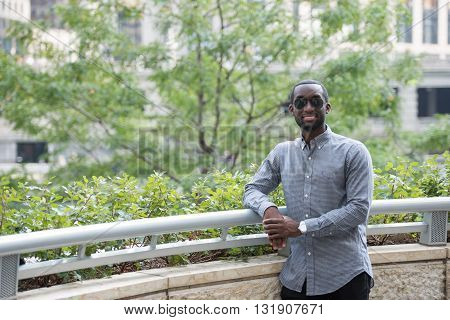 A handsome Afro-American male model in casual dress is seen standing on the balcony during  a photoshoot. On the background, green leaves of trees and balcony railings are seen.
