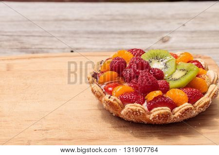Fruit tart with a yellow custard, ladyfinger cookie shell crust, raspberries, strawberries, kiwi fruit and mandarin oranges on a cutting board on a rustic farm picnic table in summer.
