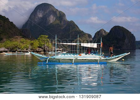 EL NIDO PHILIPPINES - FEBRUARY 05 2014 : Boats waiting for tourists to travel between the islands. El Nido is one of the top tourist destinations in the world.
