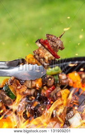 Full grill and meat skewer being hold in sticks