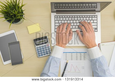 Businessman working at office table with chart and calcuator