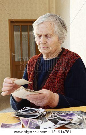 Grandma portrait Grandma sitting at home and looking at old photos