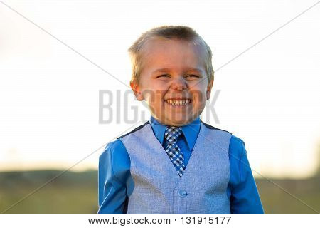 Little guy in his suit making a big smile against the summer sun