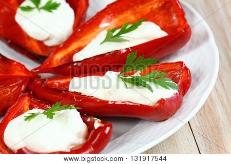 Stuffed grilled pepper.Pepper filled with cream cheese. Red stuffed pepper. Grilled pepper on the plate.