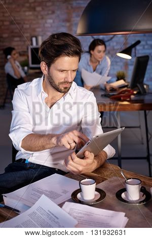 Businessman sitting at desk, working with tablet computer, concentrating.