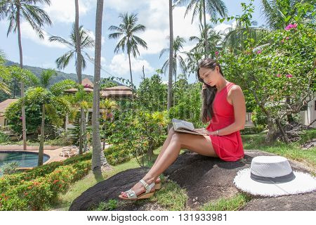 Young woman is reading a book in a tropical garden.