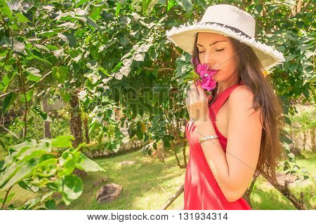 Beauty model girl enjoying nature in garden with beautiful tropical flowers. Young woman smelling flowers outdoors.